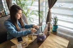 Té de consumición de la mujer en café y el trabajo foto de archivo libre de regalías