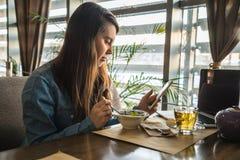 Té de consumición de la mujer en café y el trabajo imagen de archivo libre de regalías