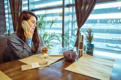 Té de consumición de la mujer en café y el trabajo fotos de archivo libres de regalías