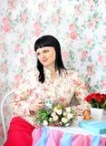 Té de consumición de la mujer en un sitle elegante lamentable Fotografía de archivo libre de regalías