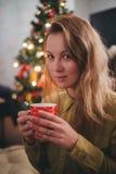 Té de consumición de la mujer joven cerca del árbol de navidad en casa Imágenes de archivo libres de regalías