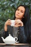 Té de consumición de la mujer joven en el café de la acera imagenes de archivo