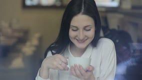 Té de consumición de la mujer joven en un café almacen de metraje de vídeo