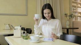 Té de consumición de la mujer joven en un café almacen de video