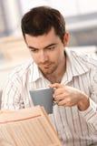 Té de consumición de las noticias de la lectura del hombre joven por la mañana Imágenes de archivo libres de regalías