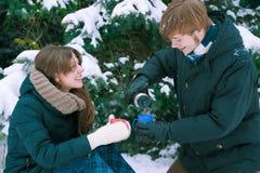 Té de consumición de los pares en invierno Imagen de archivo libre de regalías