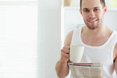 Té de consumición del hombre apuesto mientras que lee las noticias Imagenes de archivo