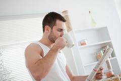 Té de consumición del hombre joven mientras que lee las noticias Imágenes de archivo libres de regalías