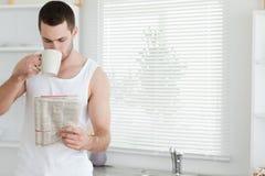 Té de consumición del hombre mientras que lee las noticias Imagen de archivo libre de regalías