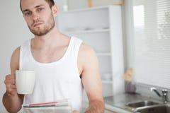 Té de consumición del hombre sano mientras que lee las noticias Imagen de archivo libre de regalías
