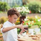 Té de consumición del muchacho agradable feliz en jardín del verde del verano Fotografía de archivo libre de regalías