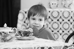 Té de consumición del niño pequeño en la tabla Fotos de archivo libres de regalías