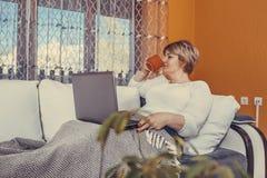 Té de consumición envejecido medio hermoso de la mujer y usar su ordenador portátil en casa imagenes de archivo