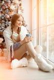 Té de consumición hermoso de la mujer joven en el árbol de navidad Beauti Imágenes de archivo libres de regalías