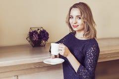 Té de consumición hermoso o café de la mujer joven Foto de archivo libre de regalías