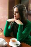 Té de consumición hermoso pensativo de la mujer joven en café Fotografía de archivo