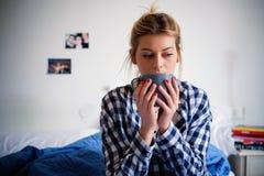 Té de consumición de la chica joven bonita y el sentarse en su cama en casa Fotos de archivo