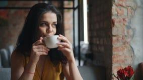 Té de consumición de la muchacha alegre en taza de la tenencia del café y sonrisa disfrutando de la bebida almacen de metraje de vídeo