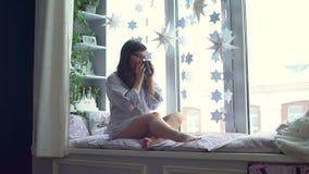 Té de consumición de la mujer en el travesaño de la ventana almacen de metraje de vídeo