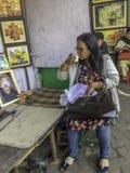 Té de consumición de la mujer en una tienda de la calle imagen de archivo libre de regalías