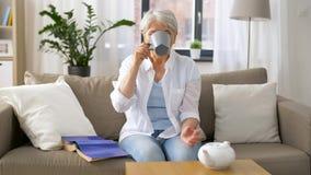 Té de consumición de la mujer mayor en casa almacen de metraje de vídeo
