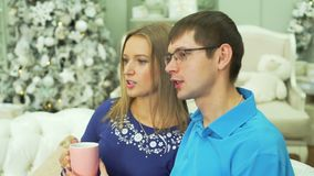Té de consumición de los pares jovenes en interior de la Navidad almacen de metraje de vídeo