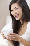 Té de consumición o café de la mujer oriental hermosa Imágenes de archivo libres de regalías