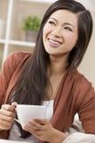 Té de consumición o café de la mujer oriental hermosa Foto de archivo