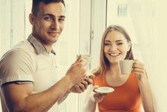 Té de consumición o café de los pares jovenes en casa Imagen de archivo libre de regalías
