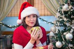 Té de consumición sonriente de la mujer en la mañana de la Navidad Imagen de archivo