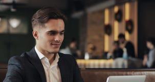 Té de consumición sonriente y usar del hombre de negocios la sentada del ordenador portátil en la tabla del café metrajes