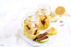 Té de hielo hecho en casa fresco infundido del agua con la fruta cítrica y el canela de la manzana dos tarros de cristal con té f Fotos de archivo