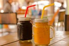 Té de hielo y café de hielo en tarros de albañil en la tabla y el fondo del restaurante en Asia Imagenes de archivo
