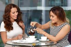 Té de la bebida de dos muchachas en café Fotografía de archivo