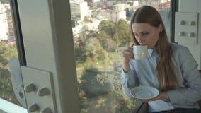 Té de la bebida de la muchacha por la ventana del restaurante de moda almacen de video