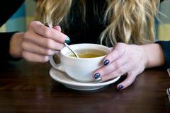Té de la bebida de la mujer en un café Fotos de archivo libres de regalías