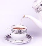 Té de la gota de la tetera a la taza de té Imagenes de archivo