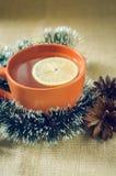 Té de la Navidad con el limón en las guirnaldas de un fondo Fotografía de archivo libre de regalías