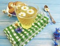 té de manzanilla, galleta del aciano en un fondo de madera Foto de archivo