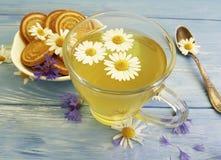 té de manzanilla, refresco de la galleta del aciano en un fondo de madera Fotografía de archivo