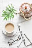 Té de Masala, tetera, libreta, vidrios, pluma, hoja verde de la flor en el fondo blanco, visión superior Planeamiento de la inspi imagen de archivo