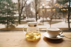 Té de un espino amarillo en una tetera transparente en una tabla de madera en una ventana que hace frente a la calle Fotografía de archivo