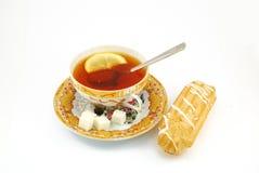 Té del desayuno con el limón y el eclair Imágenes de archivo libres de regalías