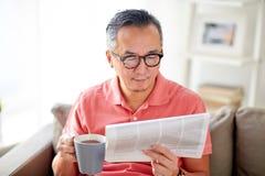 Té del hombre y de la lectura periódico de consumición en casa Imagen de archivo
