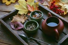 Té del otoño, tetera en un fondo de madera, hojas de otoño Fotografía de archivo