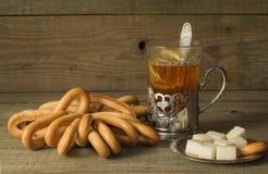 Té en el soporte de vaso, los panecillos y el azúcar imagen de archivo