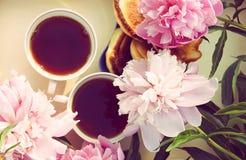 Té en estilo rural en jardín del verano en el pueblo Dos tazas de té negro en la bandeja de madera y las flores florecientes de l imagenes de archivo