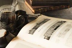 Té en la tabla de trabajo con los artículos vintages Fotos de archivo
