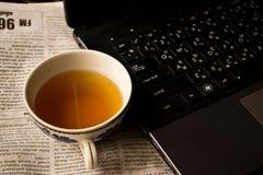 Té en la taza blanca en una tabla con un ordenador y un periódico Foto de archivo libre de regalías