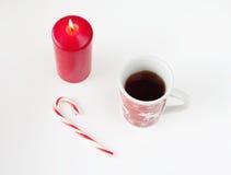 Té en taza de la Navidad, caramelo de la Navidad y vela roja Foto de archivo